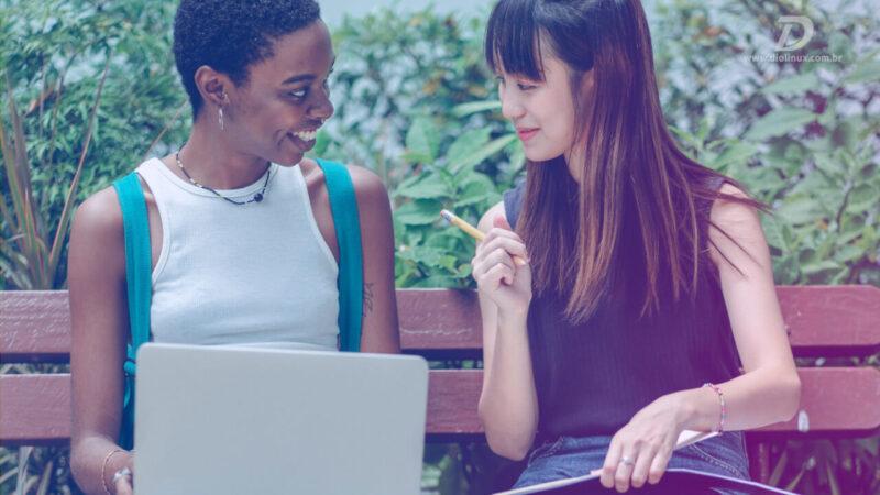 Duas mulheres sentadas em um banco conversando, enquanto uma segura um notebook e a outra um caderno.